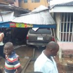 WOMAN ESCAPES DEATH AS CAR RAMS INTO HER SHOP